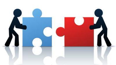 due omini stilizzati spingono due pezzi di un puzzle rosso e blu per unirli