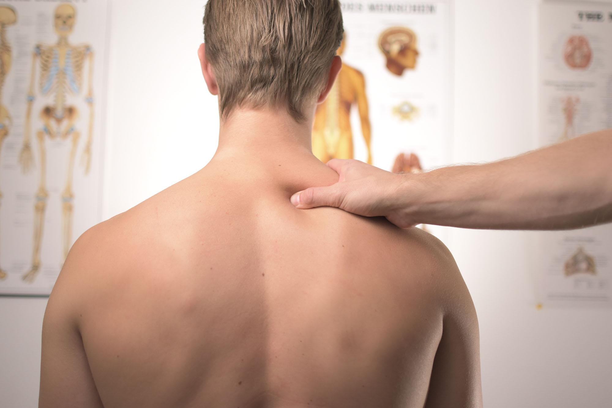 uomo di spalle, che ha subito un colpo di frusta, la mano dell'osteopata è appoggiata sul suo collo