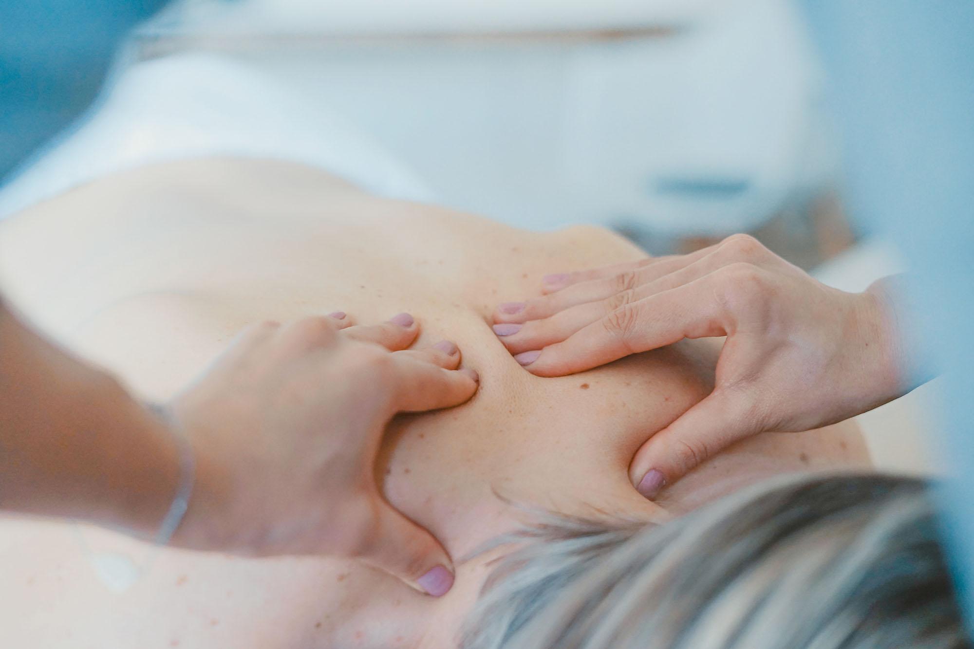 Un massaggiatore sta eseguendo un massaggio sulla schina di una donna